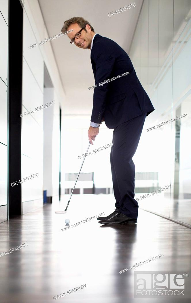 Stock Photo: Businessman putting golf ball in office.