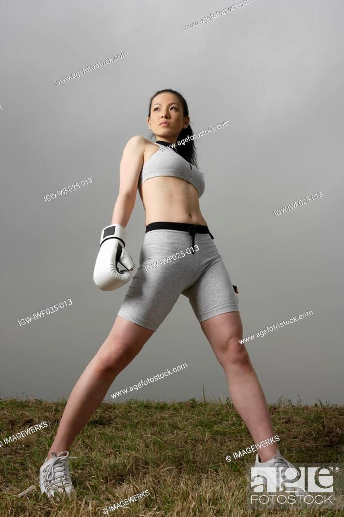 Stock Photo: View of a young woman standing with boxing gloves.