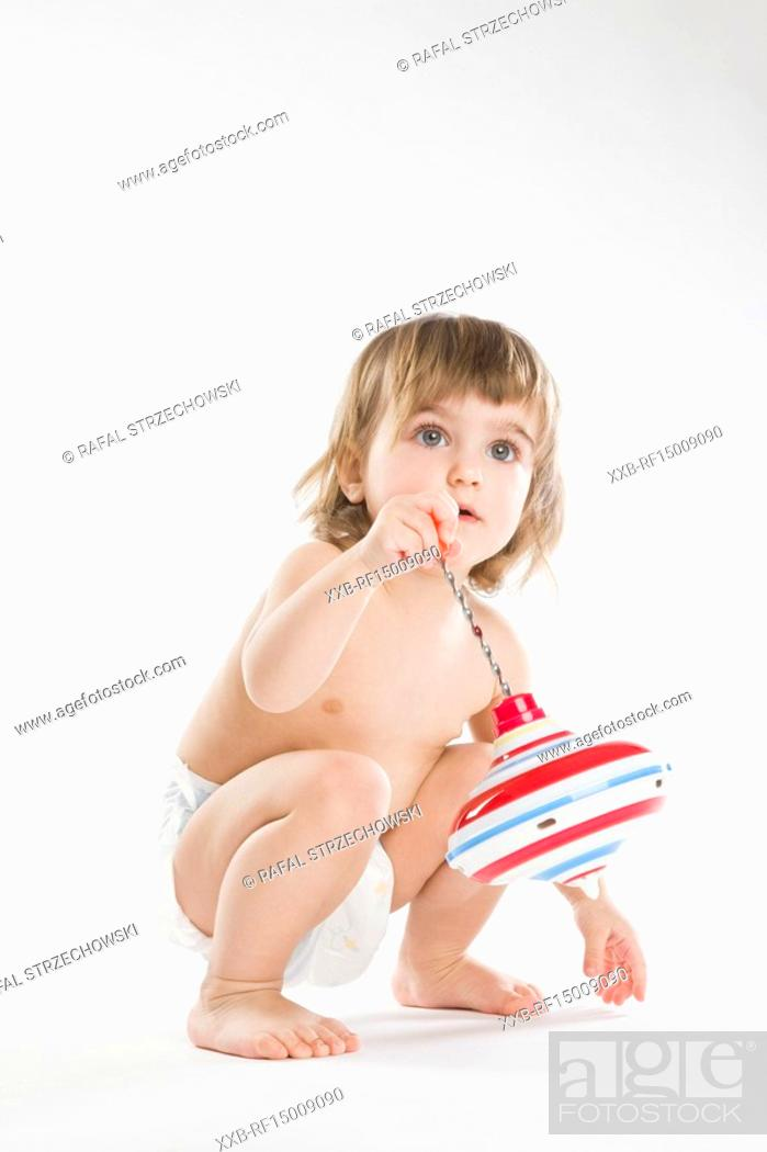 Imagen: toddler girl playing with spinning top.
