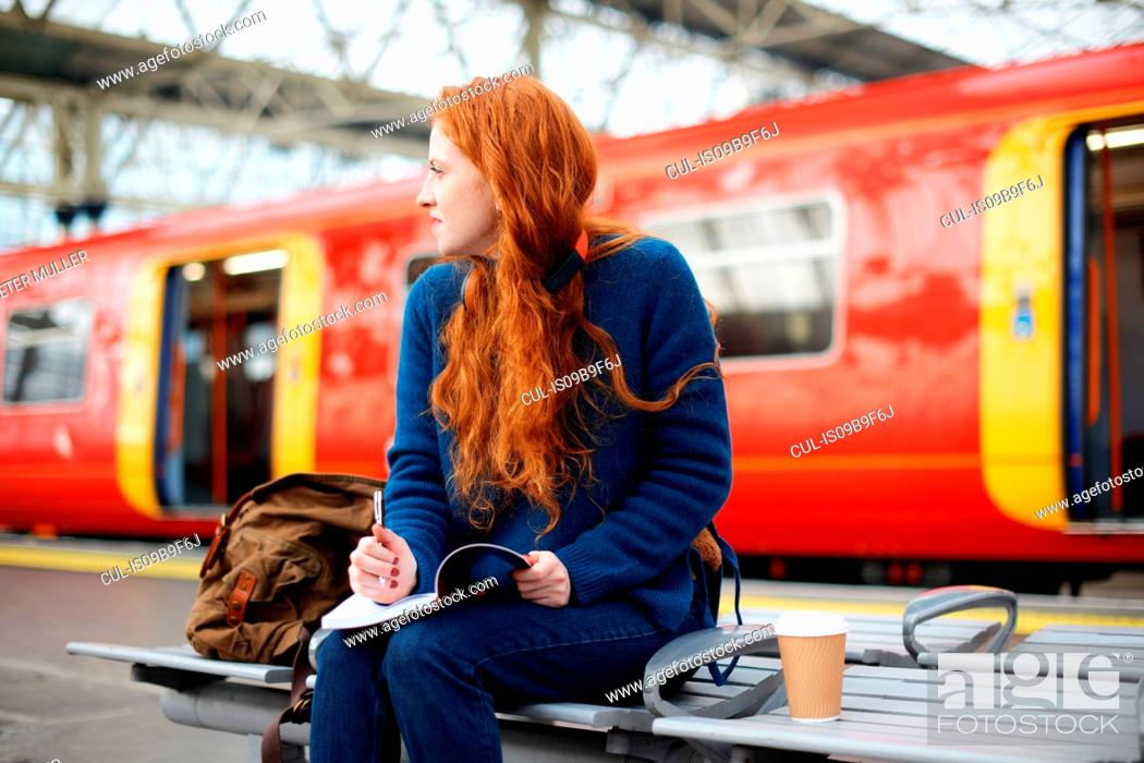 Stock Photo: Woman on bench on train station platform, London.