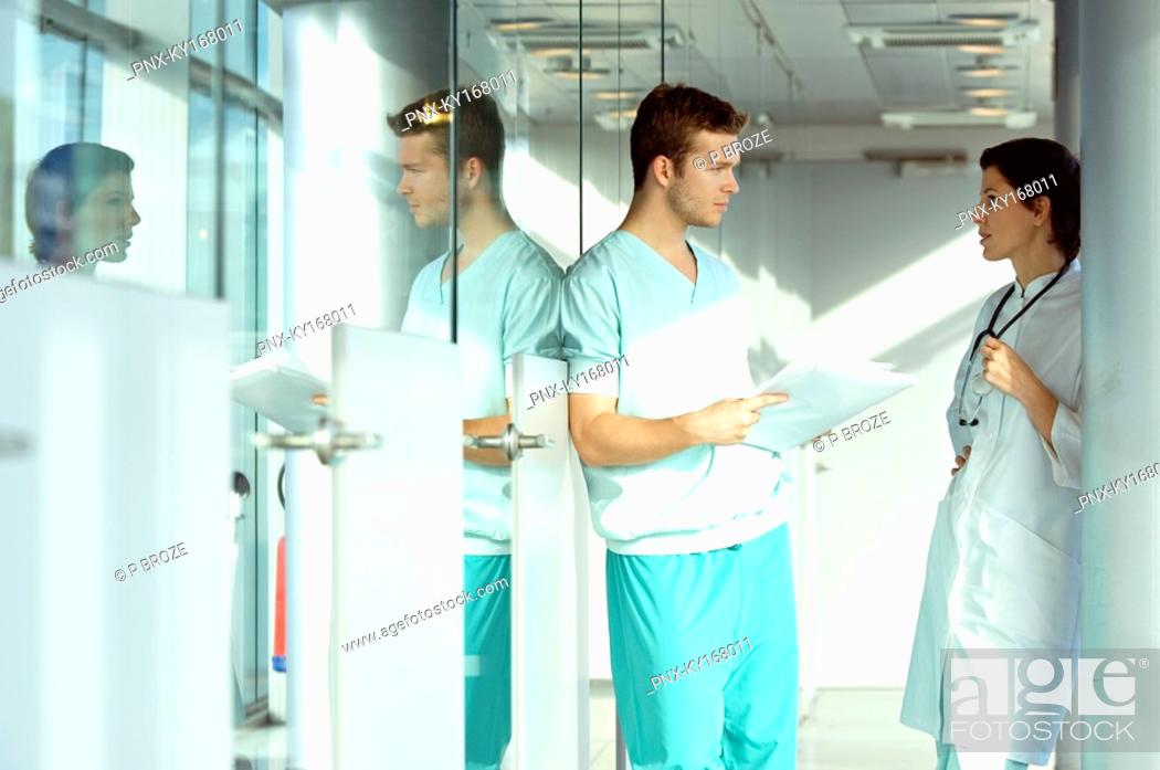Stock Photo: Side profile of two doctors discussing a medical record.