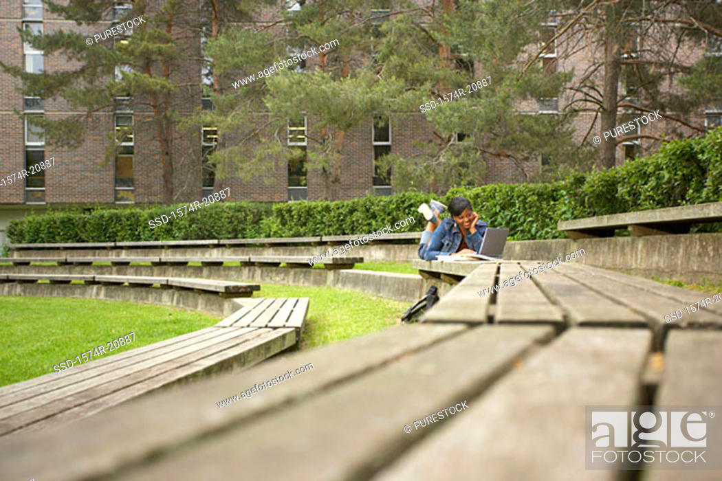 Stock Photo: College student lying on a bench and using a laptop.