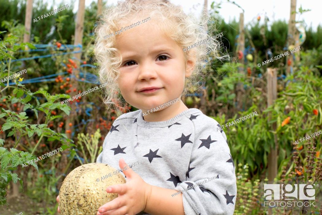 Stock Photo: Little girl with cantaloupe in garden.