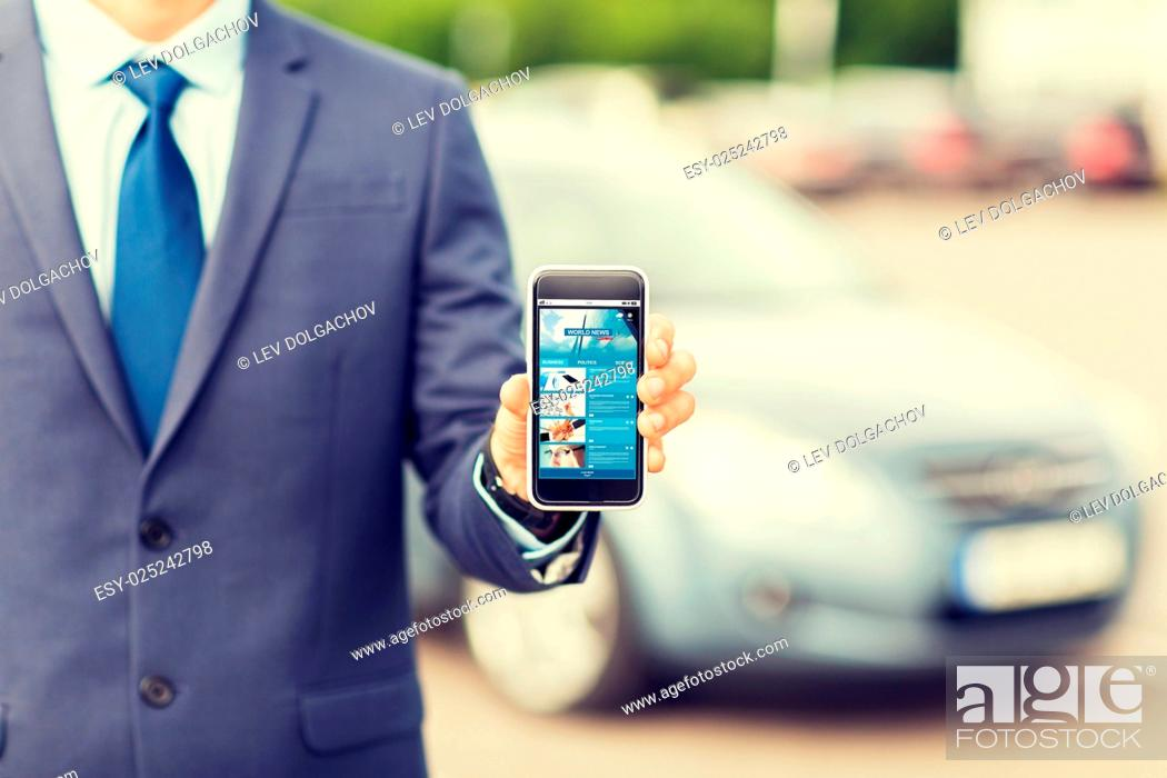 Stock Photo: transport, business trip, mass media, technology and people concept - close up of man showing internet news page smartphone screen on car parking.