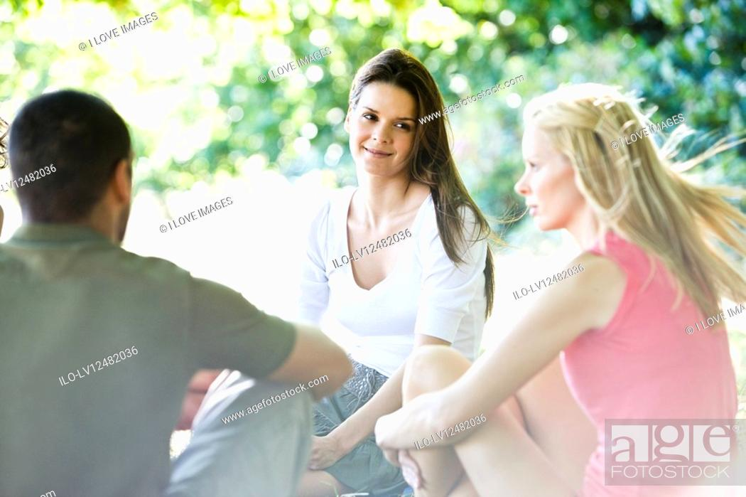 Stock Photo: Three friends sitting outdoors in summertime.