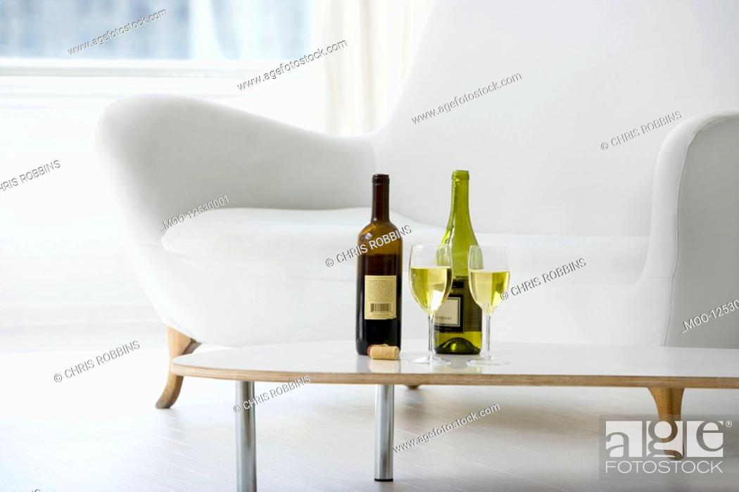 Stock Photo: Wine glasses and bottles on coffee table in living room.