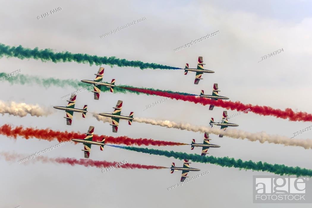 "Stock Photo: LINATE MILAN, ITALY October 12 2019 - military jets of Italian Aerobatic Military team """"PAN"""" come across with tricolor smoke at airshow."