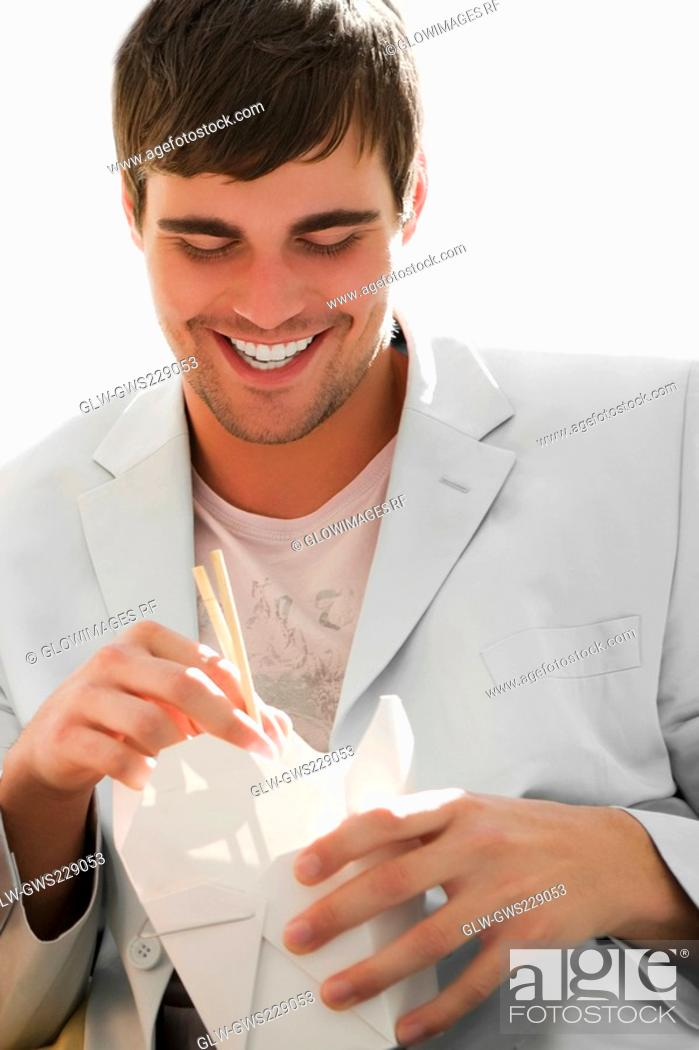 Stock Photo: Close-up of a young man holding chopsticks and smiling.