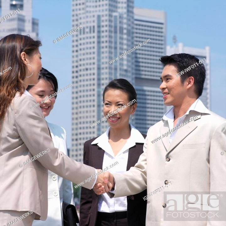 Stock Photo: Low angle view of a businessman shaking hands with a businesswoman.