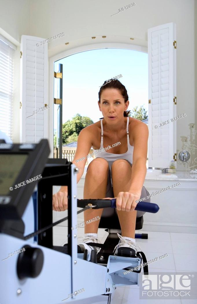 Stock Photo: Young woman using exercise machine.