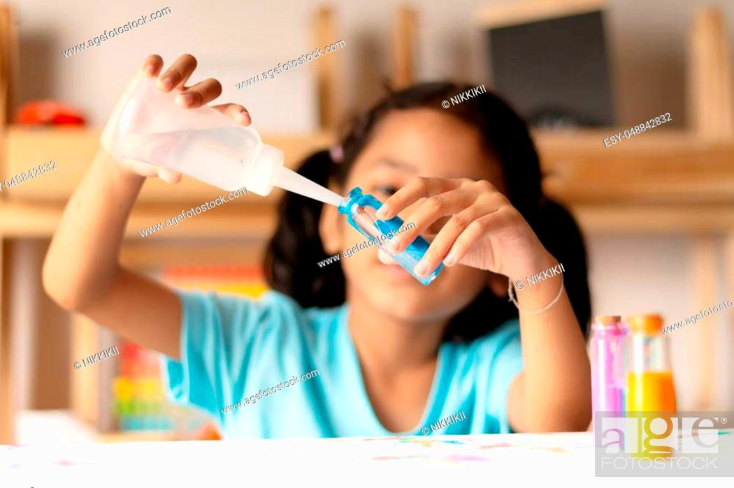 Stock Photo: Asian girl is pouring water into a glass of blue color to experiment. Select focus shallow depth of field.