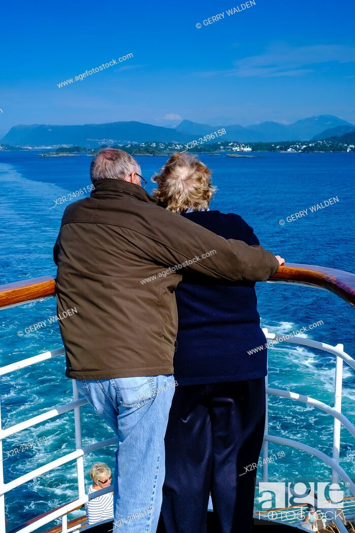 Stock Photo: A couple looking back over a ships rail whilst leaving port in the Norwegian fjords.