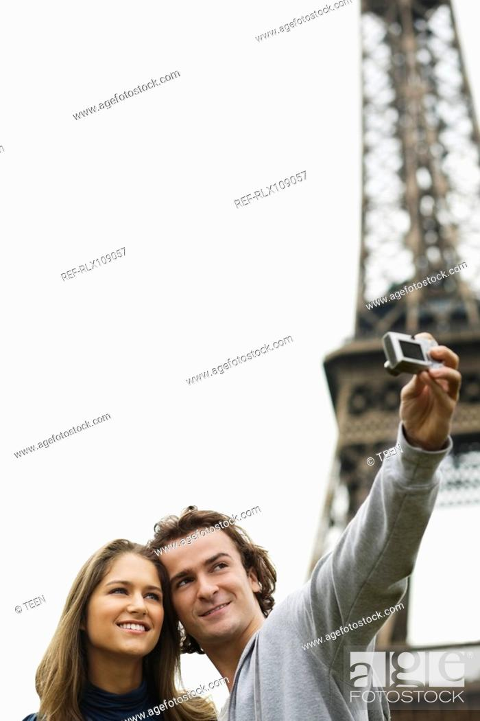 Stock Photo: Young couple in front of Eiffel tower man taking photo, Paris, France.
