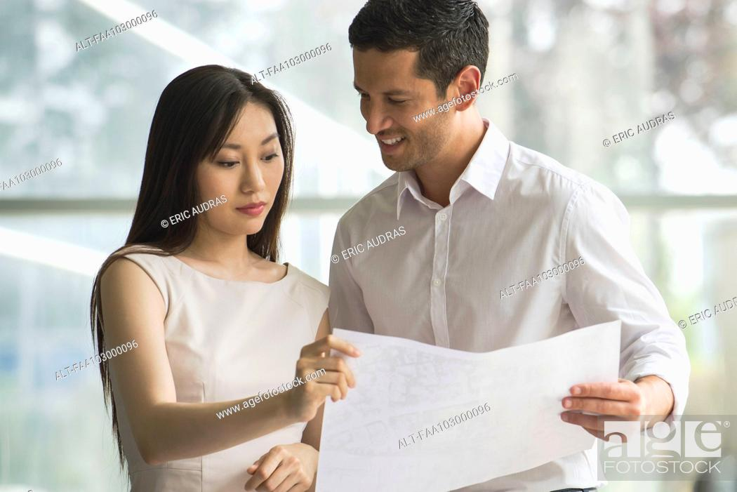 Stock Photo: Designers reviewing blueprint together.