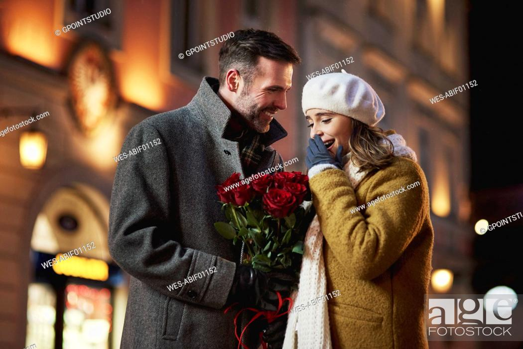 Stock Photo: Man giving his girlfriend bunch of red roses on Valentine's Day.