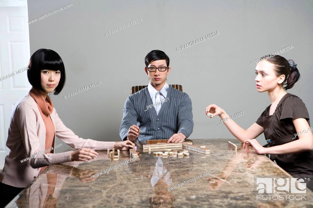 Stock Photo: two fashionable women and a man playing mahjong.