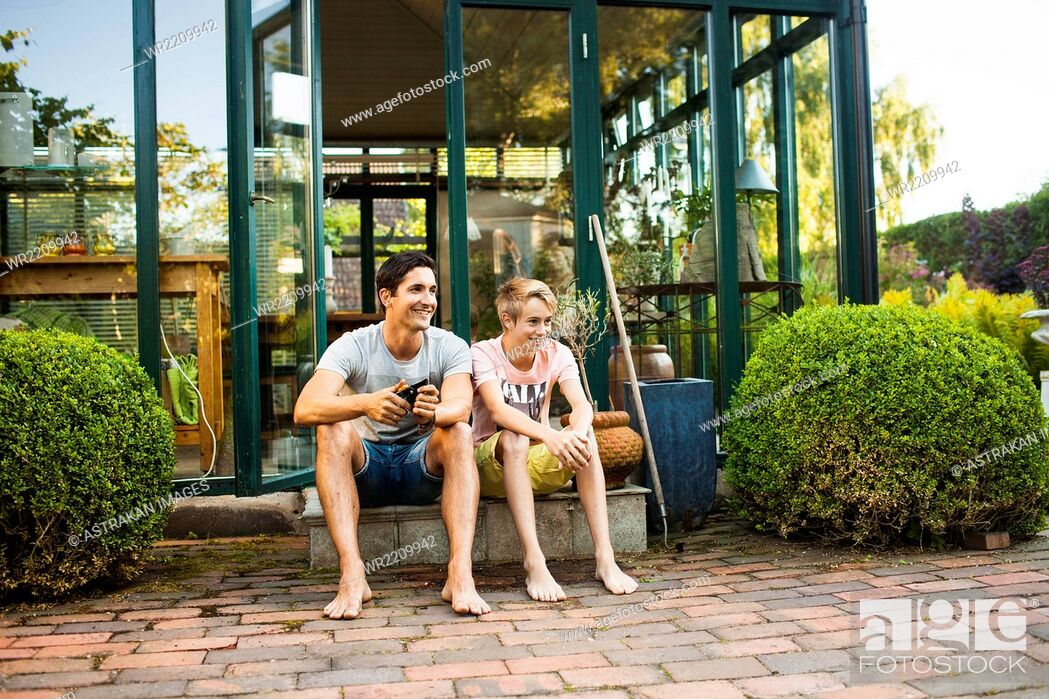 Stock Photo: Full length of happy father and son sitting outside house.