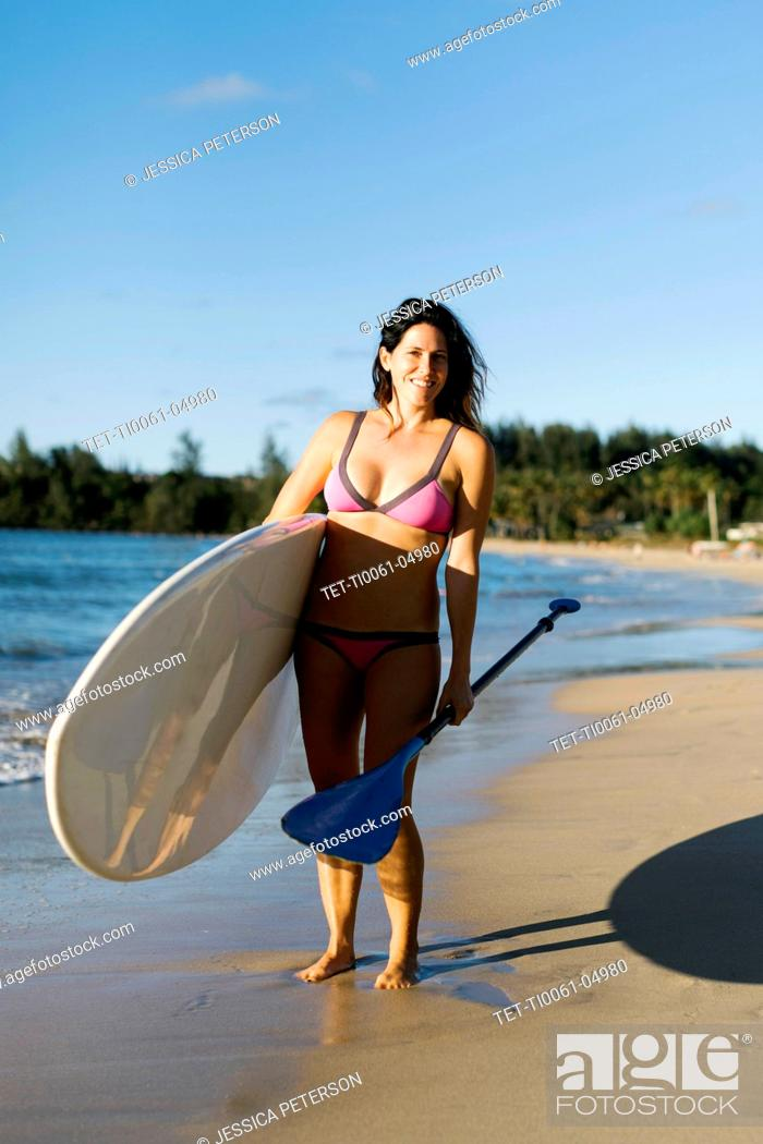 Photo de stock: Woman with paddleboard and oar on beach.