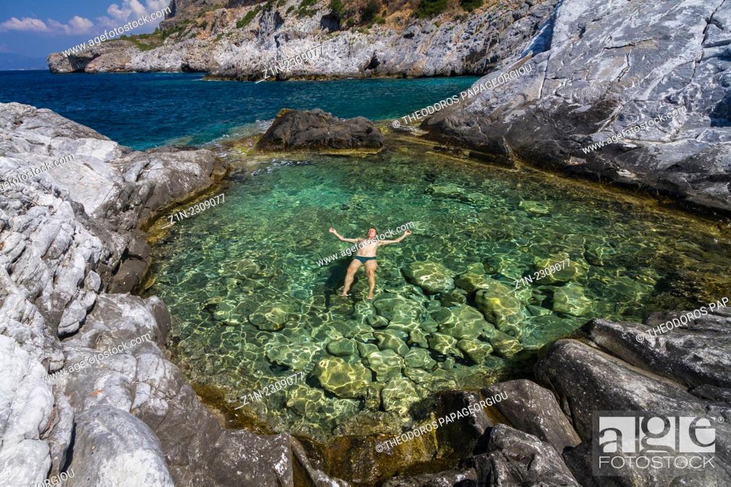 Stock Photo: A man relaxing on the water of a natural pool with sea water. Trachila village, Messenia, Greece.