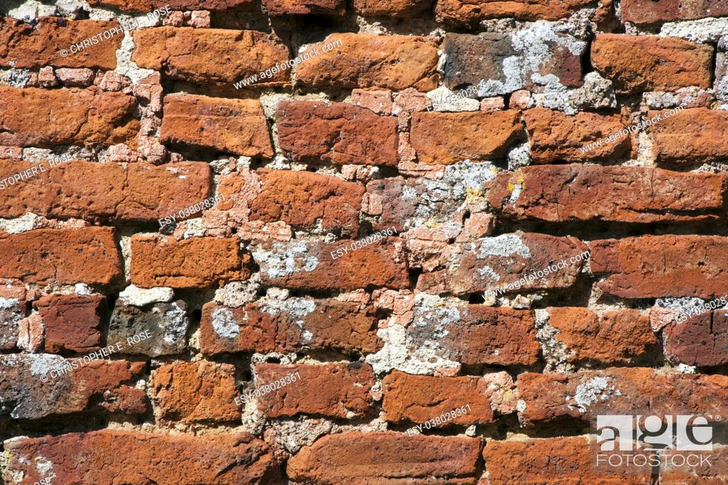 Stock Photo: Very old weathered, damaged, badly repaired hand made red brick wall close up.