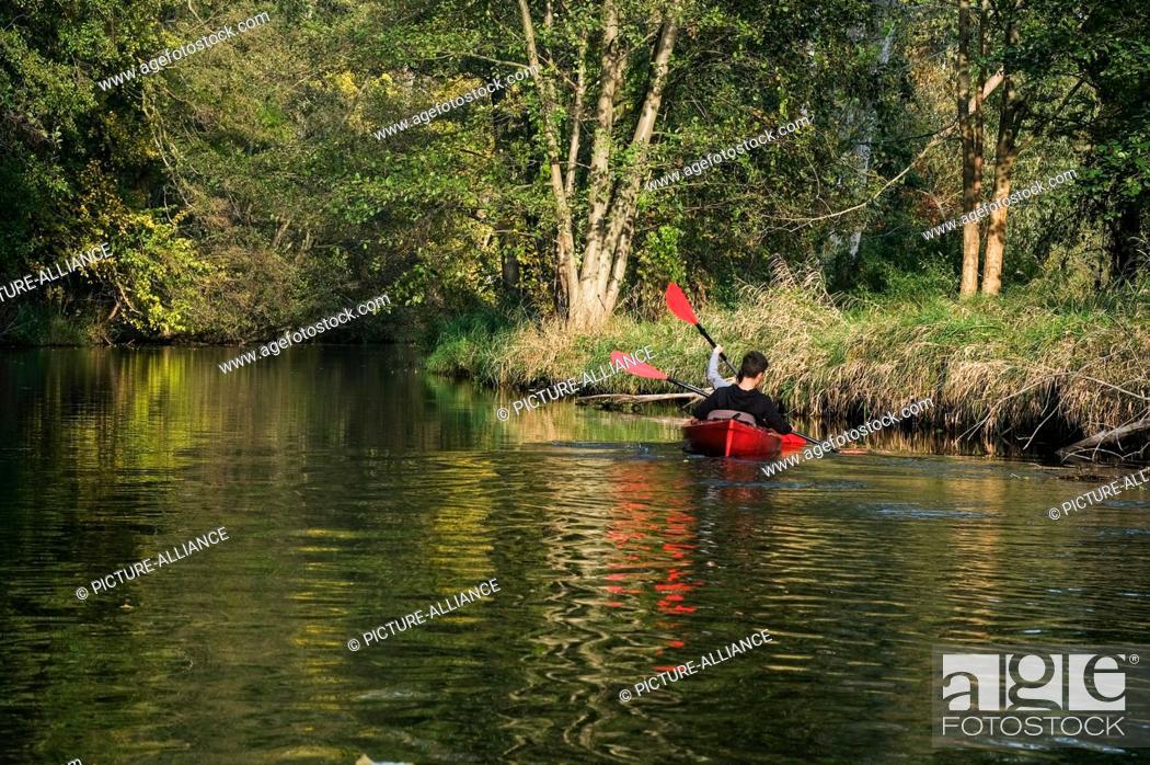 Stock Photo: 25 October 2020, Brandenburg, Schlepzig: A canoe is on its way on the main Spree in the Spreewald. Photo: Jens Kalaene/dpa-Zentralbild/ZB.