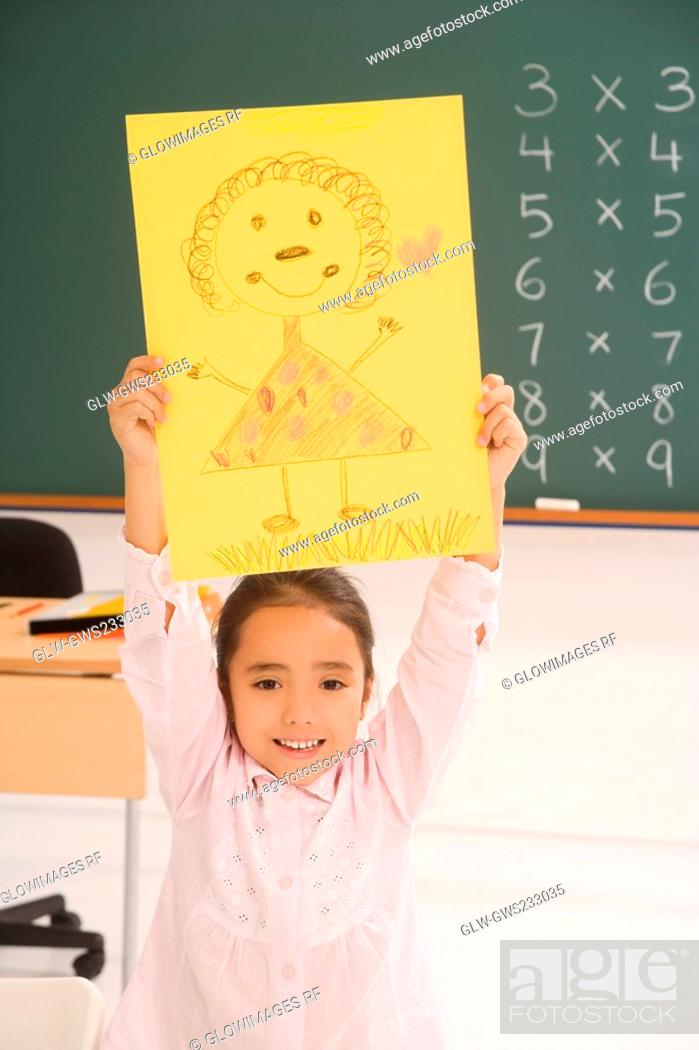 Stock Photo: Portrait of a schoolgirl showing her drawing and smiling.