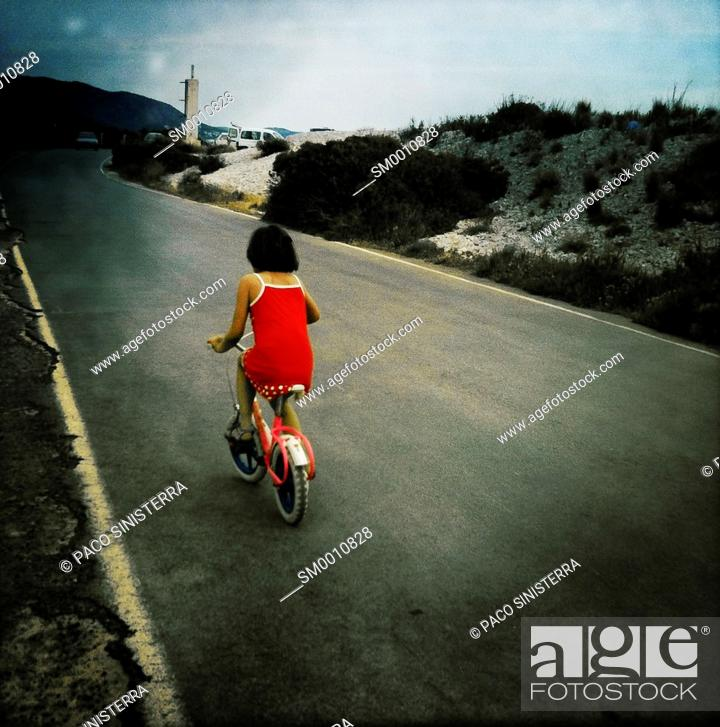 Stock Photo: Girl learning has cycling on the beach of Benicassim, Castellon, Valencia, Spain.