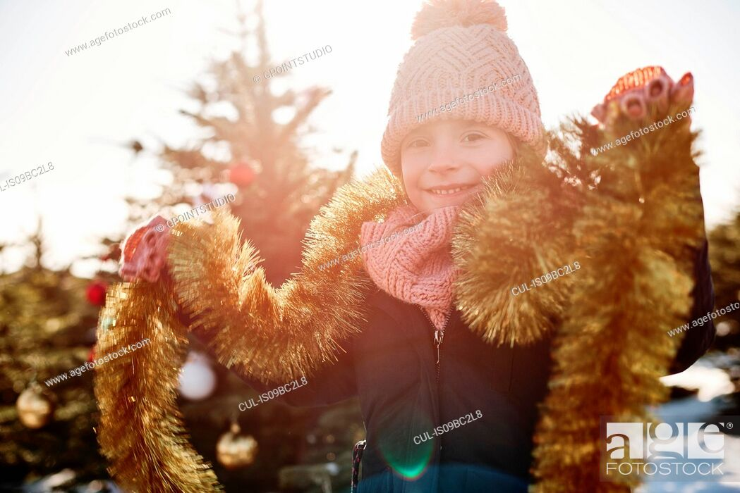 Stock Photo: Girl in christmas tree forest wearing tinsel, portrait.