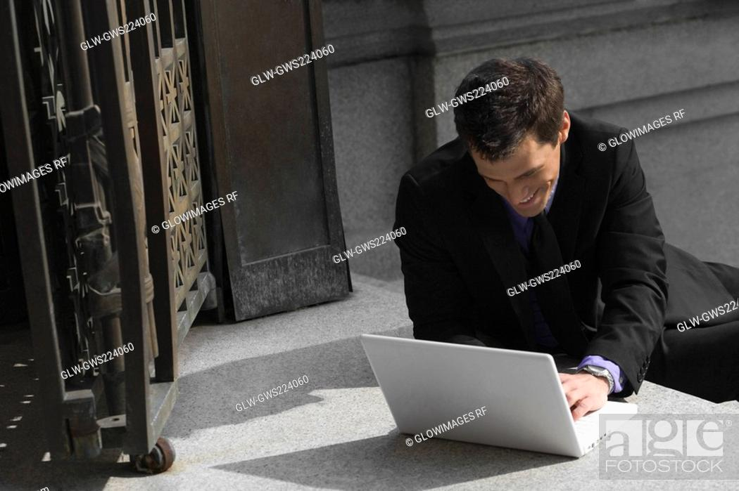 Stock Photo: Businessman sitting on steps and using a laptop.