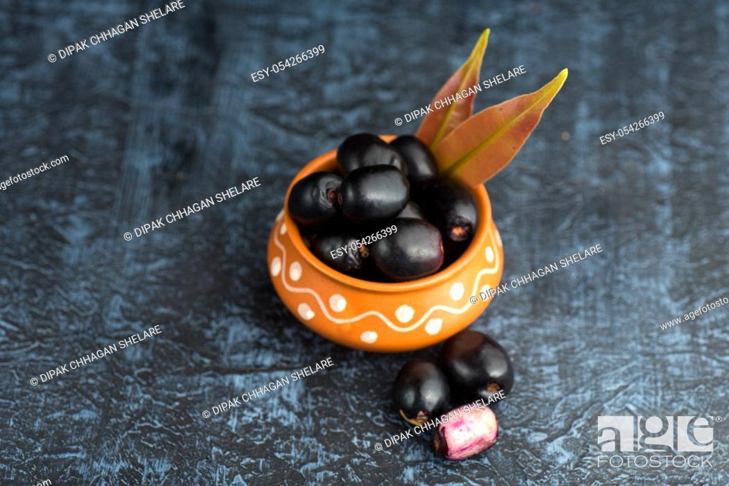 Stock Photo: Jambolan plum or jambul or Jamun fruit, Java plum (Syzygium cumini) with leaf on stone textured background.