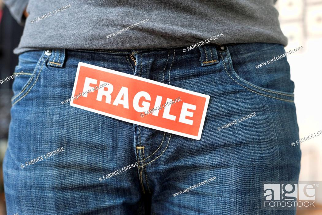Stock Photo: Midsection view of a person with a word 'Fragile' stuck on its jeans.