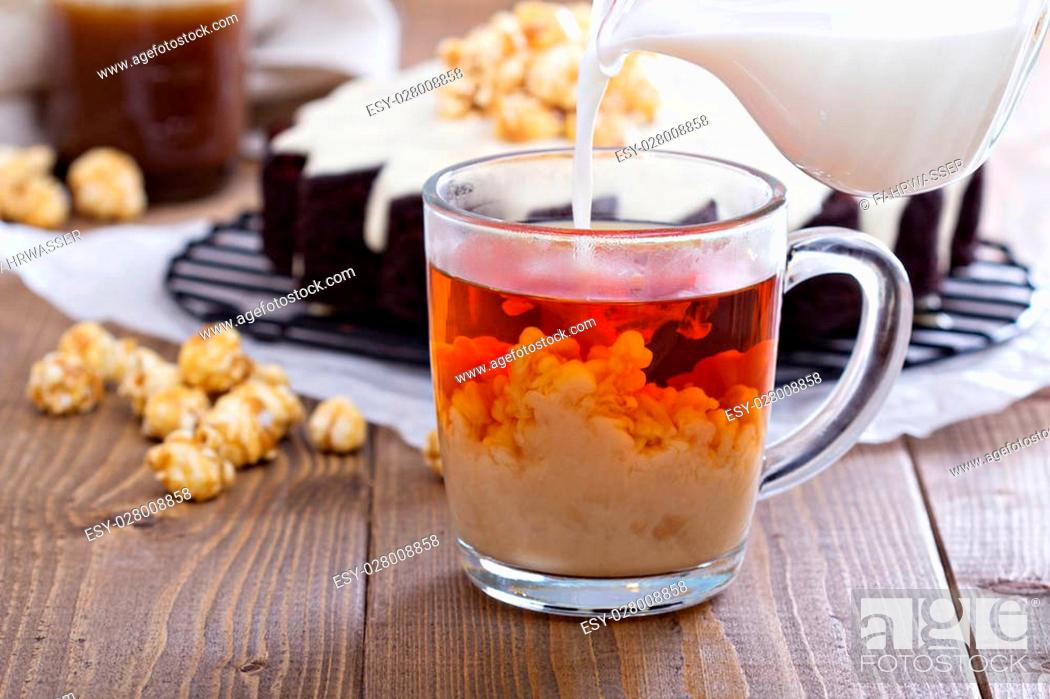 Stock Photo: Cup of black tea with milk pouring over.
