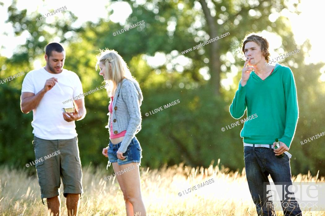 Stock Photo: Three young friends standing in a field, eating, drinking and smoking.