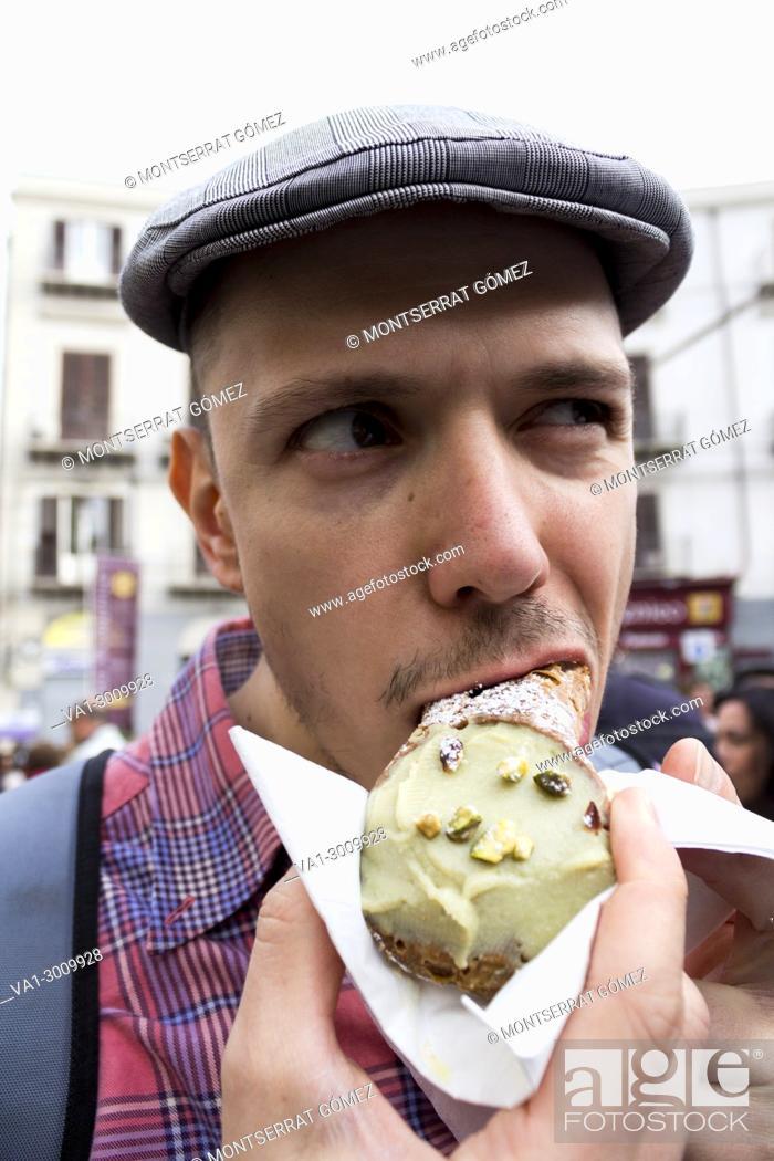Imagen: Young man eating a Sicilian pistachio cannolo. Palermo, Sicily. Italy.