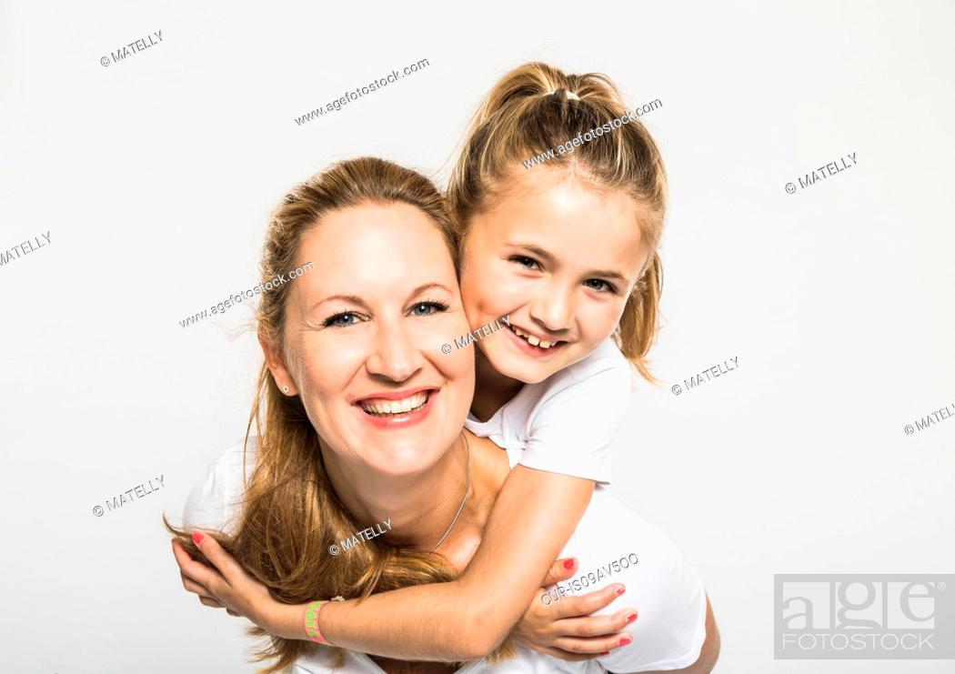Imagen: Studio portrait of happy girl getting piggyback from mother.