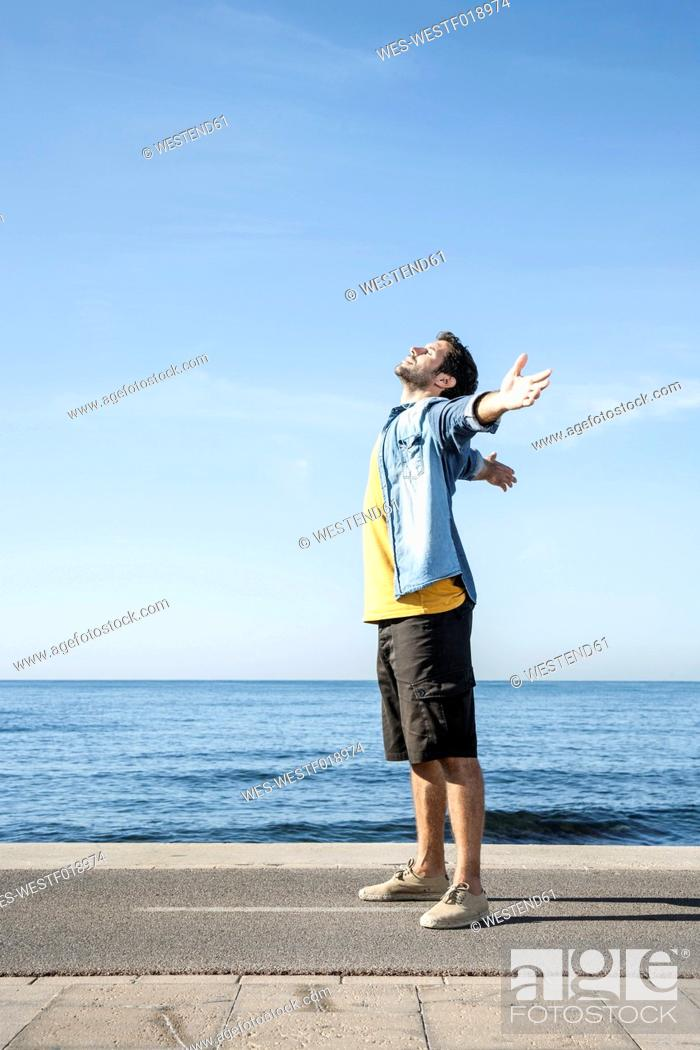 Stock Photo: Spain, Mid adult man standing at Atlantic Ocean.