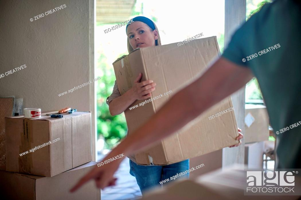 Stock Photo: Moving house: couple lifting cardboard boxes.