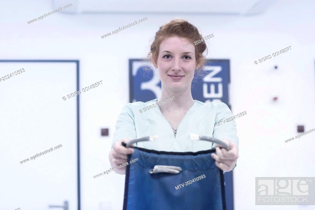 Stock Photo: Portrait of young nurse holding body protector against x-ray.