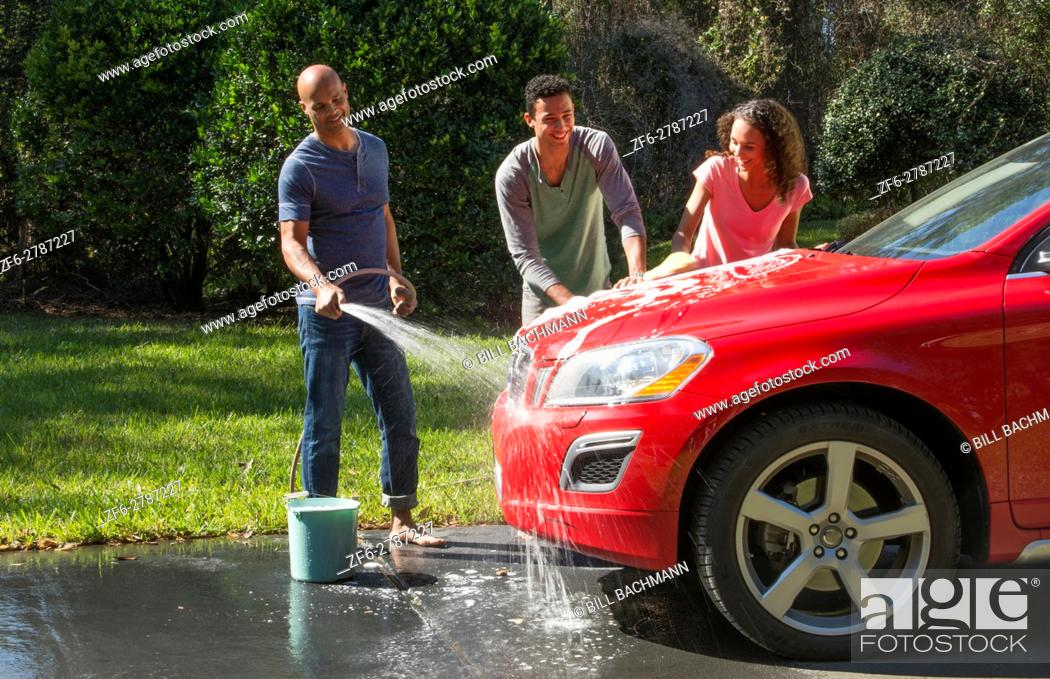 Stock Photo - Family wash car at home black Caribbean dad son and daughter  outside in sun red car fun together love Model Released, MR-16, MR-18,  MR-20.