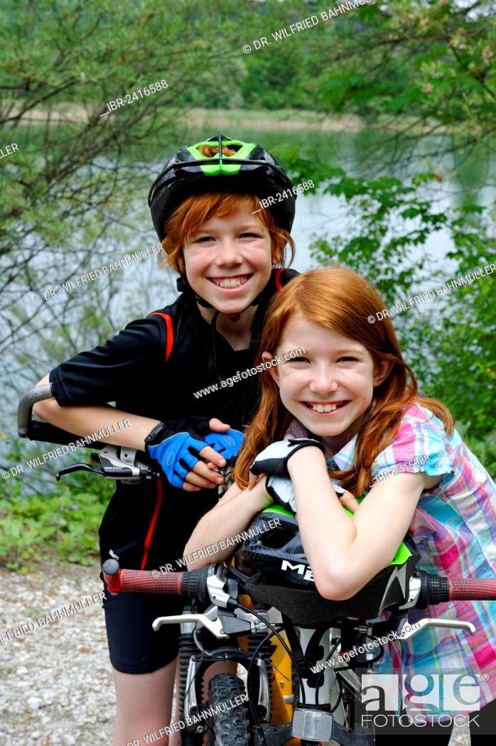 Imagen: Two children, boy and girl, with mountain bikes and helmets.