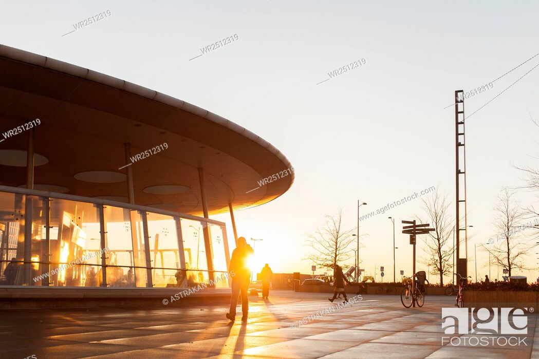 Stock Photo: Silhouette person walking outside modern building during sunset.
