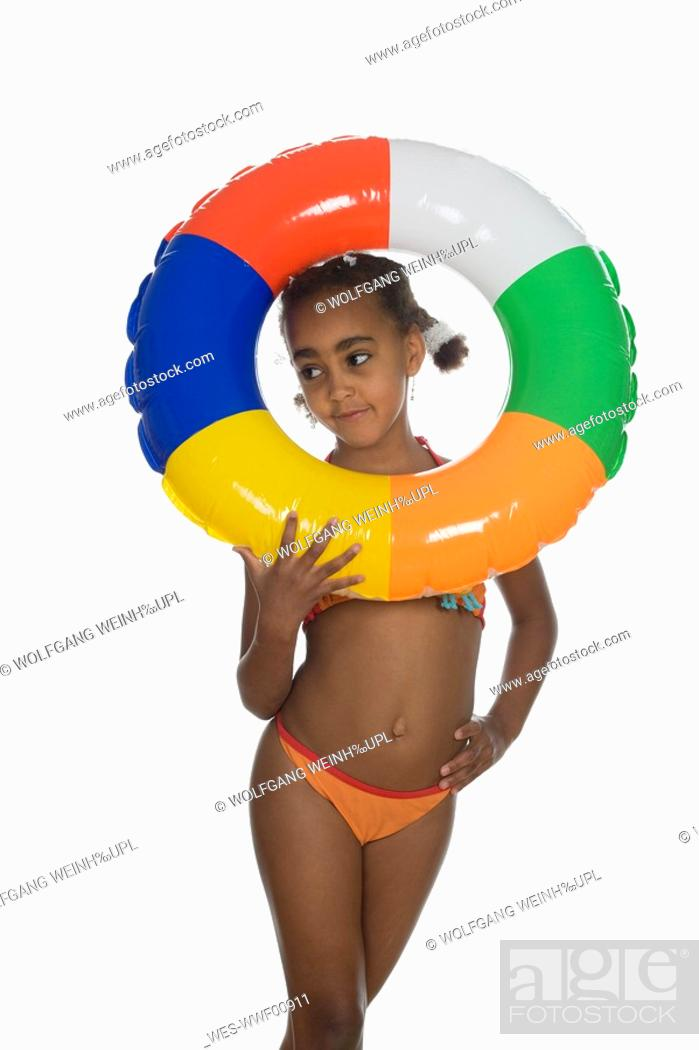 Stock Photo: African girl 6-7 holding floating tire, portrait.