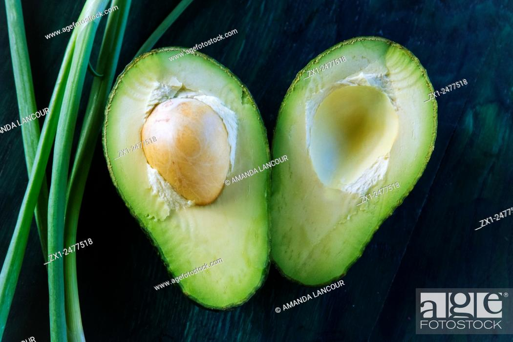 Imagen: Cross section of an avocado halved with seed in tact, with a spring onion accent on greenish blue textured wooden background.