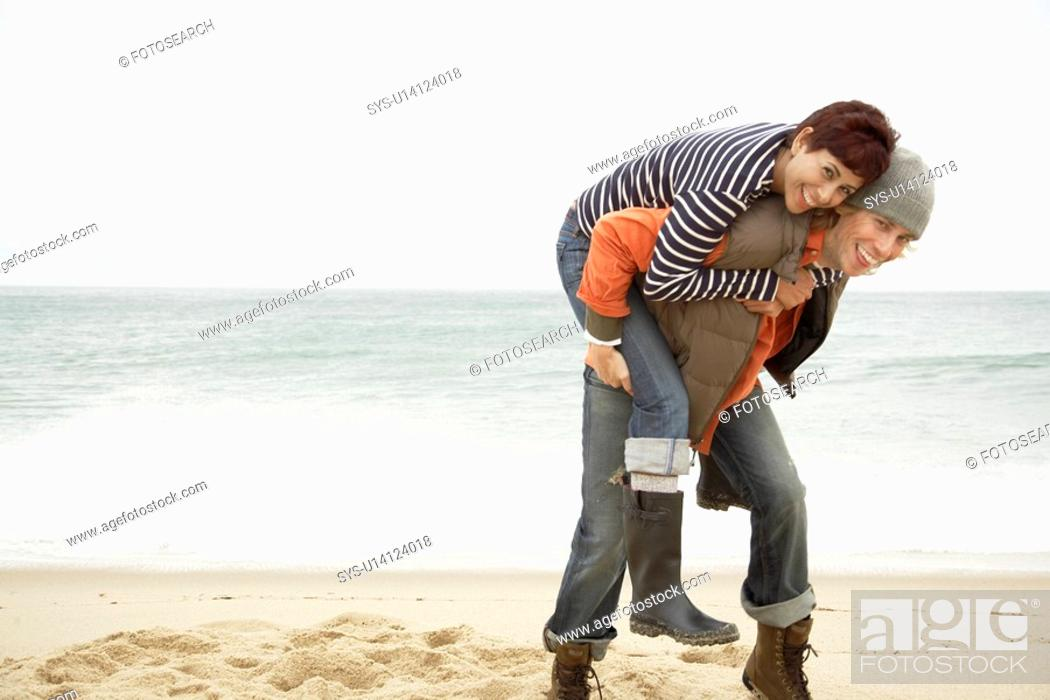 Stock Photo: Man giving woman piggyback on beach.