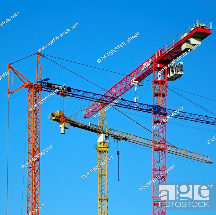 Stock Photo: Three construction cranes / tower crane against blue sky.