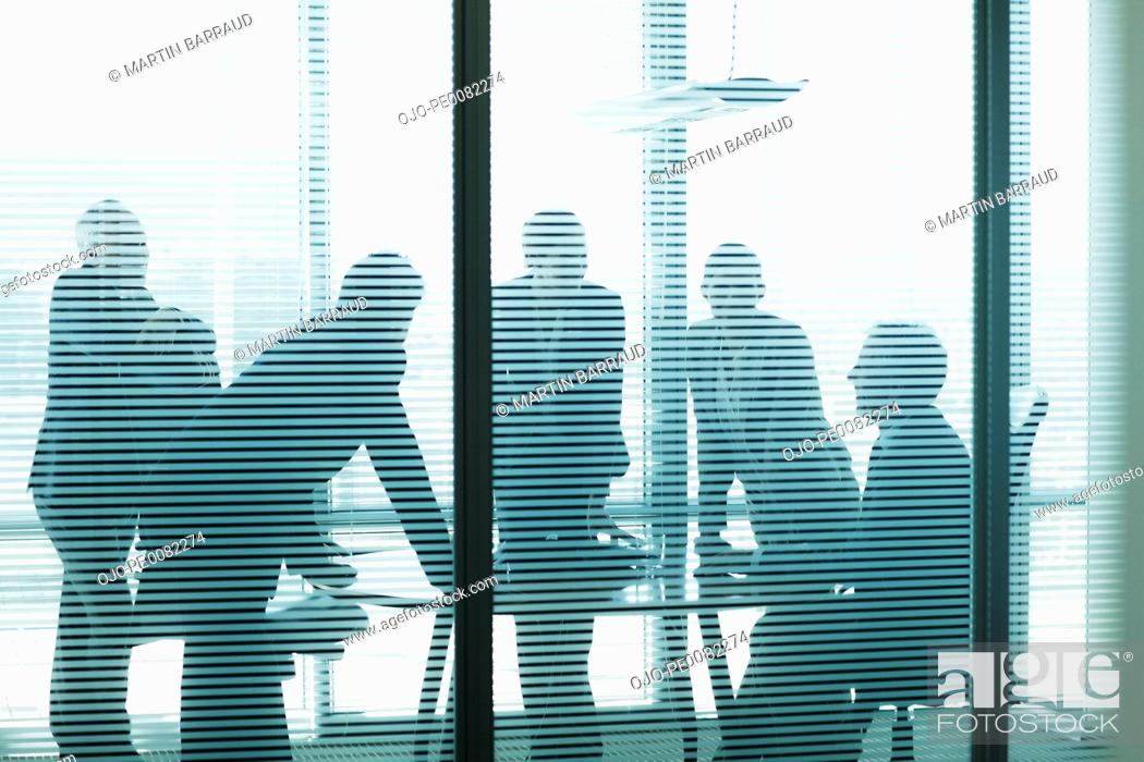 Stock Photo: Silhouette of business people leaning on table in conference room.