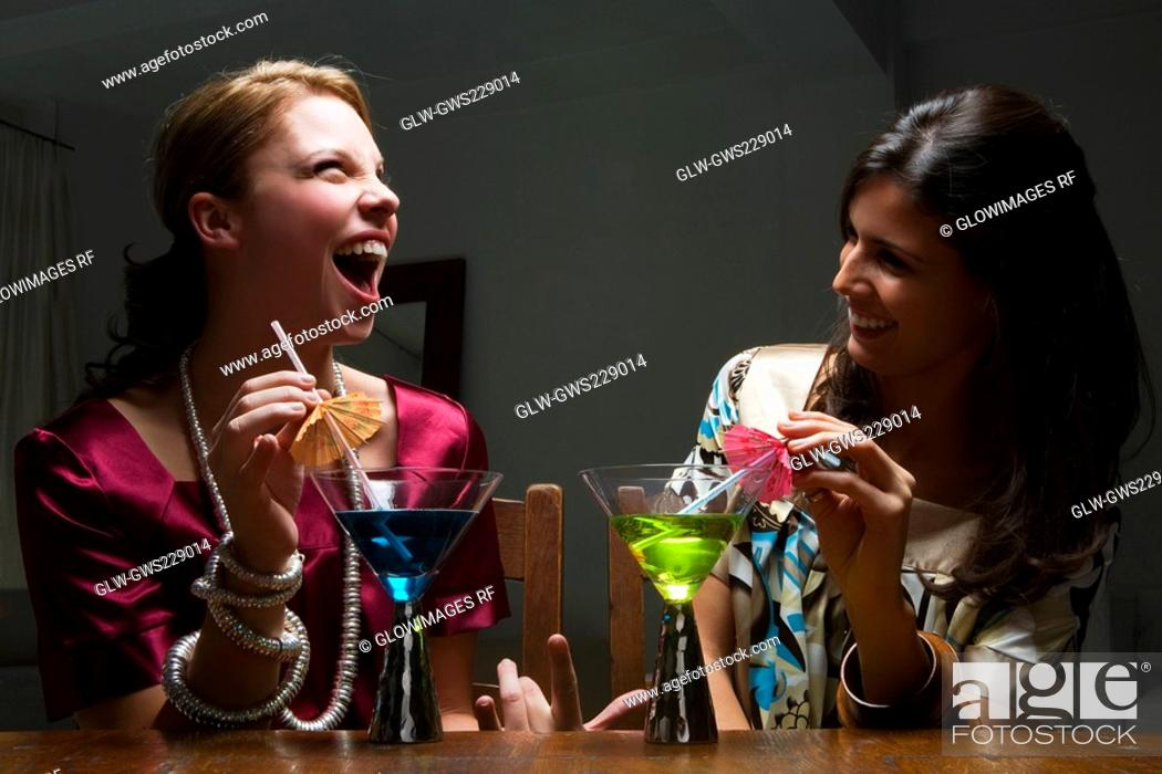 Stock Photo: Two young women drinking cocktail and smiling.
