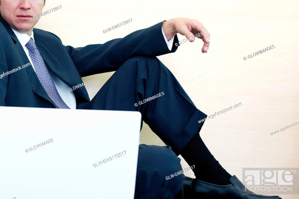 Stock Photo: Businessman sitting in front of a laptop.