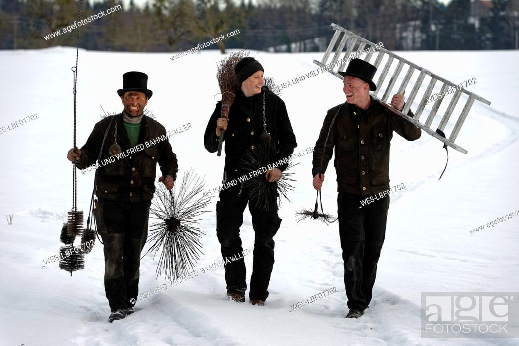 Stock Photo: Three laughing chimney sweeps walking in snow.
