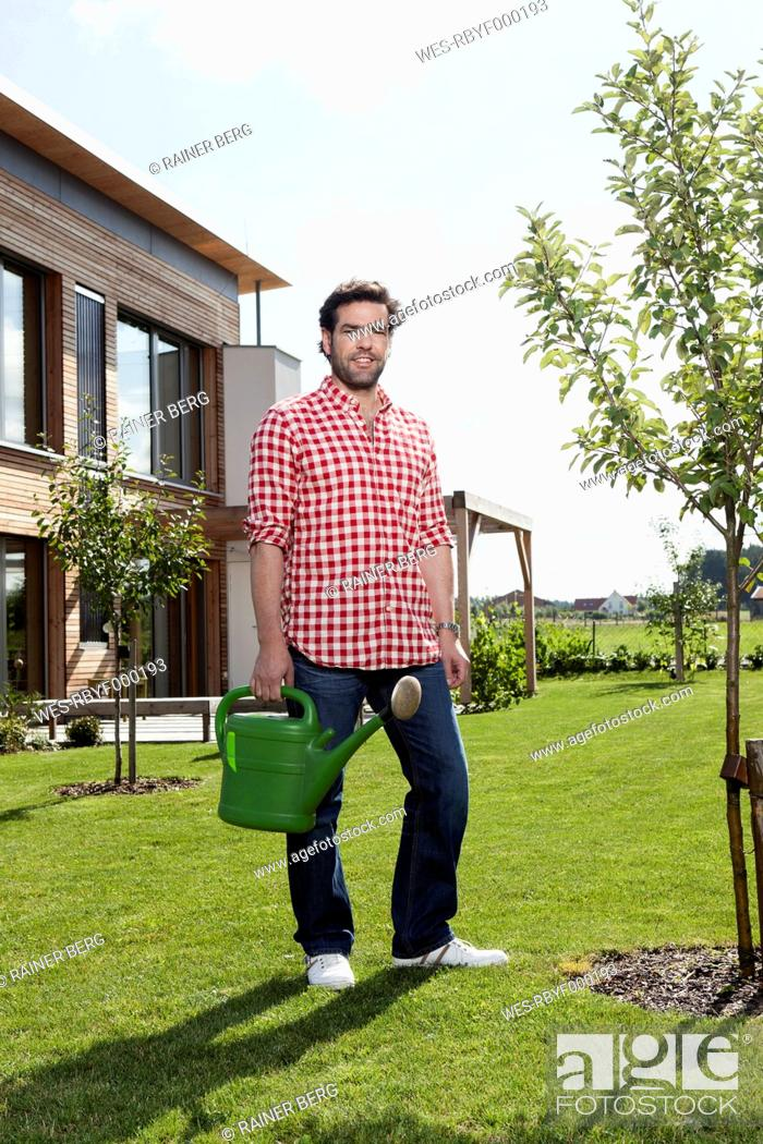 Stock Photo: Germany, Bavaria, Nuremberg, Mature man with watering can in garden.